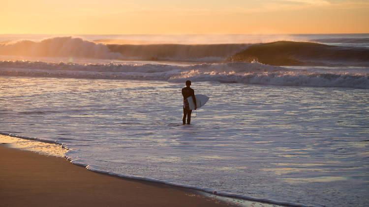uomo con tavola da surf in spiaggia